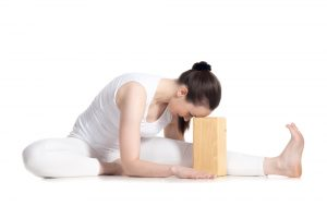 Sporty beautiful young beginning yoga student in white sportswear sitting in head to knee forward bend pose leaning on wooden block, doing Janu Sirsasana variation, studio full length isolated shot